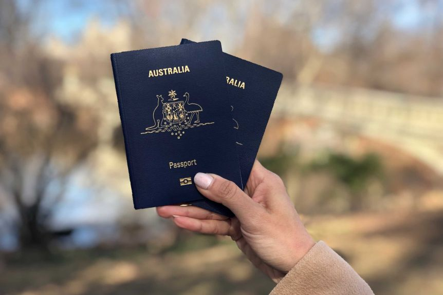 A hand holds two Australian passports in Central Park, New York.